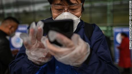 A passenger wearing a face mask uses a smartphone to scan a Wuhan city health QR code before entering the Tianhe Airport.