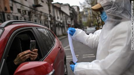 A woman wearing a hazmat suit and face mask holds up a Wuhan city health QR code for residents to scan before entering a residential compound in Wuhan.