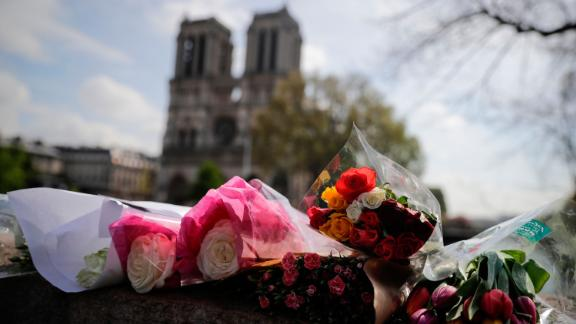 Flowers are laid on a bridge in front of Notre Dame on April 17, 2019.