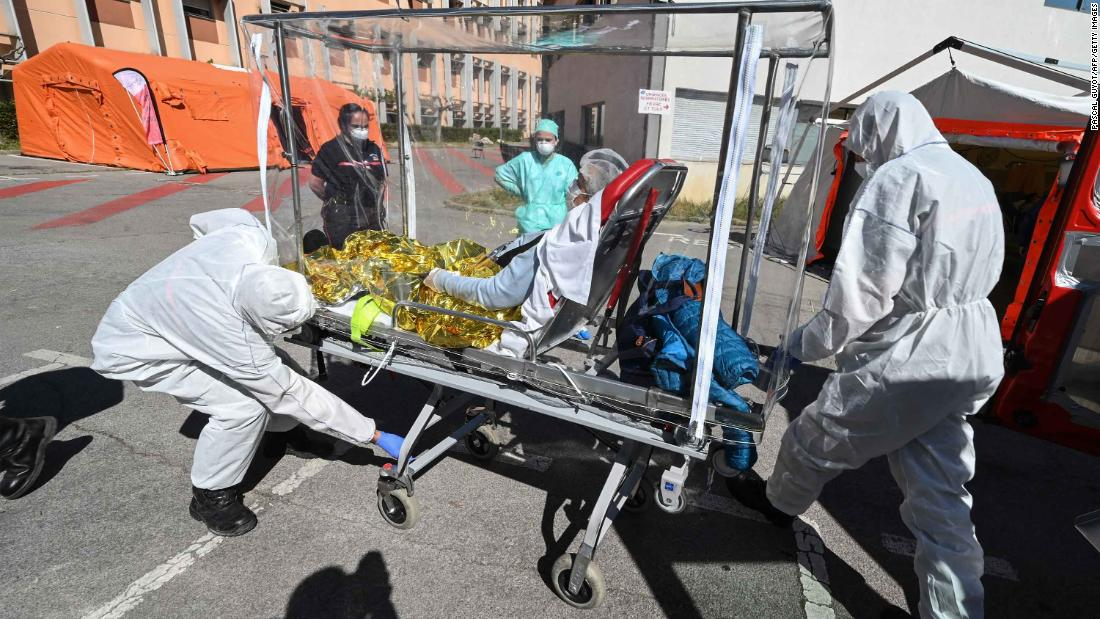 Firefighters transfer a patient from an ambulance in Montpelier, France, on April 14, 2020.