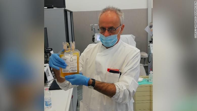 Doctor Cesare Perotti, director of the immunotransfusion service at the University of Pavia San Matteo Hospital, holds a bag of plasma after a donation.