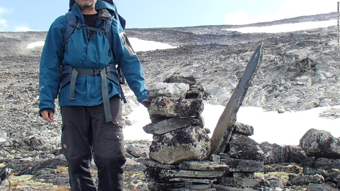 Researcher Lars Pilø is pictured by a cairn, which was used to mark the route of the mountain pass.