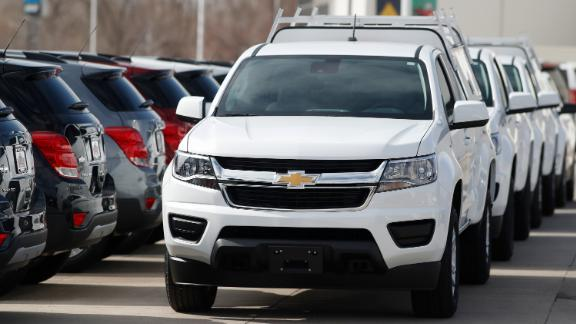 In this Sunday, March 15, 2020, photograph, a long row of unsold 2020 Colorado pickup trucks sits at a Chevrolet dealership in Englewood, Colo. (AP Photo/David Zalubowski)