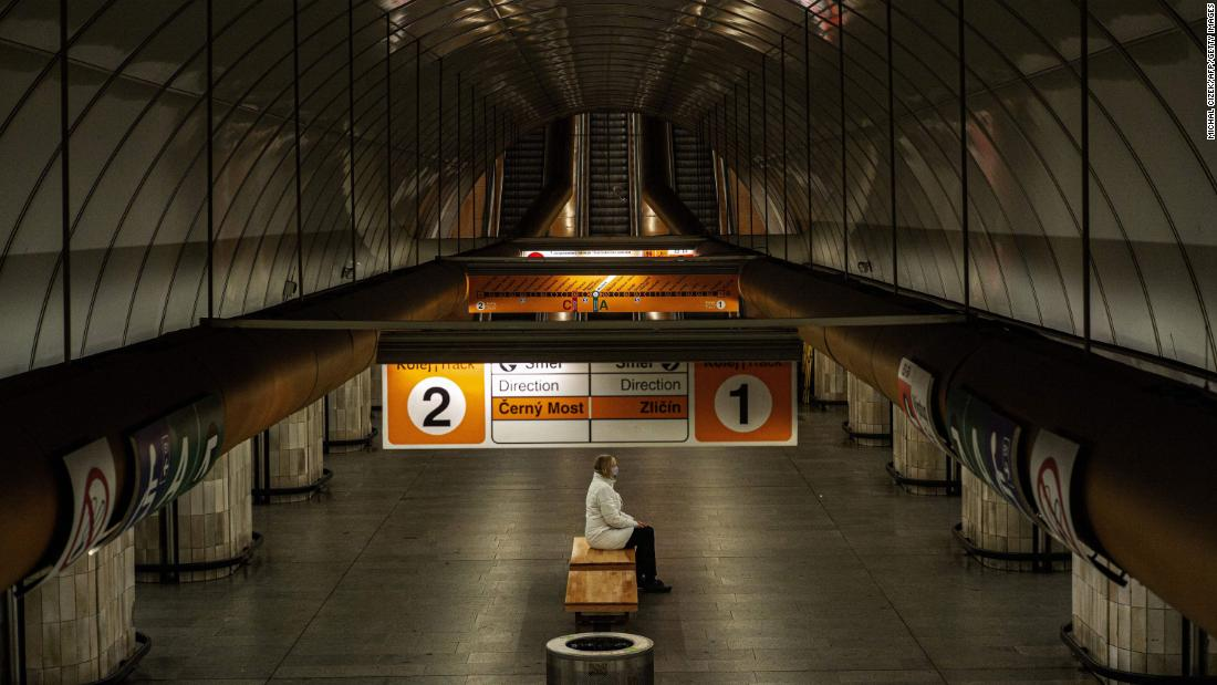 A woman sits on a bench at an empty metro station in Prague, Czech Republic.