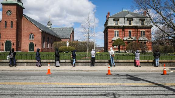 People line up for food assistance in Waltham, Massachusetts, in April.