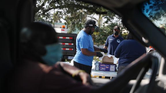 Volunteers and city employees prepare to hand out bags of food at a drive-through site in Opa-locka, Florida, in April. The food was provided by the food bank Feeding South Florida.