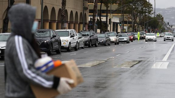 A line of cars waits to receive food at a distribution site in Van Nuys, California, in April.