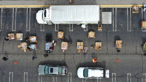 Volunteers with Forgotten Harvest load food into vehicles at a mobile pantry in Detroit.