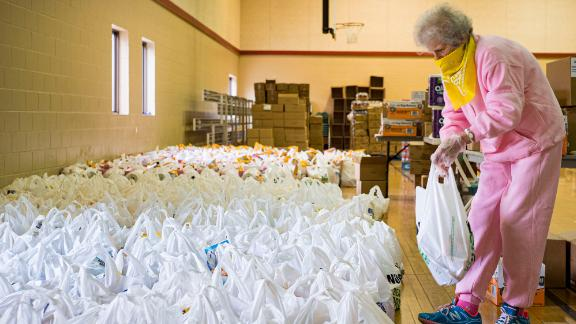 Volunteer Maria Cunningham sorts through bags of food before distributing them at a church in Des Moines, Iowa, in April.