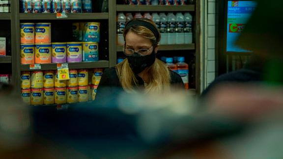 A grocery cashier wears a face mask in Brooklyn. Expect face masks to become part of the new normal of American life.