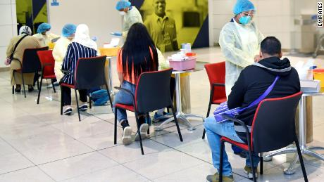 The Dubai Health Authority carries out coronavirus screening on passengers heading to Tunisia on a repatriation flight.