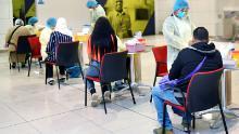 The Dubai Health Authority carries out coronavirus screening on passengers heading to Tunisia on a repatriation flight.