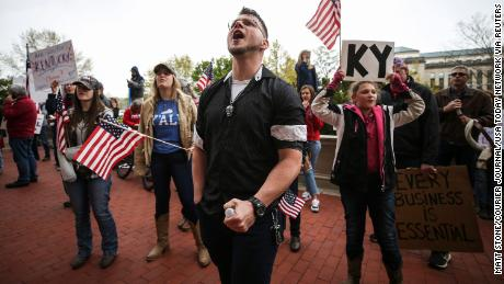 """Protestors yell """"Open Up Kentucky!"""" and """"You're not a king, we won't kiss your ring"""" outside the room where Gov. Andy Beshear was giving his daily coronavirus update on April 15 in Frankfort, Kentucky."""