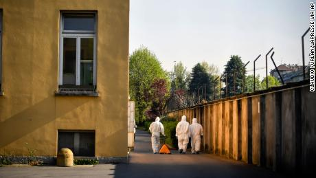 Staffers wearing protective outfits walk at the Pio Albergo Trivulzio nursing home in Milan on Tuesday, April 7, 2020.