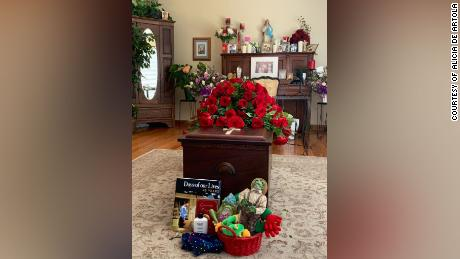 A small group of mourners gathered for a home Mass honoring Martha Palacios. More than 100 others participated in the service online.