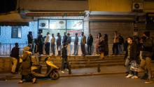 People queue at shops for food shortly before the curfew in Istanbul, on April 10, 2020.