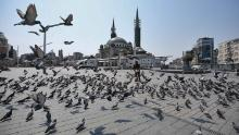 Pigeons fly around a deserted Taksim Square after a two-day curfew imposed to stem the spread of coronavirus in Istanbul.