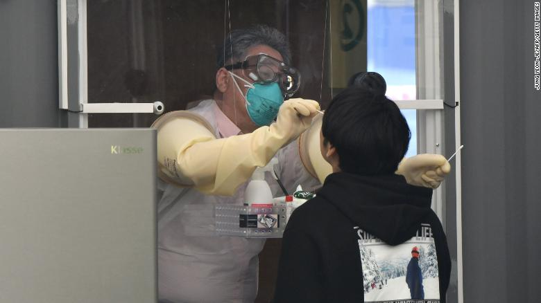 A medical staff member in a booth takes samples from a visitor for the Covid-19 coronavirus test at a walk-thru testing station set up at Jamsil Sports Complex in Seoul on April 3, 2020.