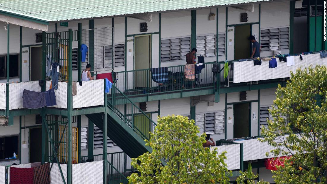 Men stand along a balcony of a dormitory used by foreign workers at Cochrane Lodge 2, which has been made an isolation area to prevent the spread of the COVID-19 novel coronavirus, in Singapore on April 17, 2020. - Singapore late on April 16 reported a record jump in coronavirus cases, most of them linked to packed dormitories housing foreign workers, as it battled a second wave of infections. (Photo by Roslan RAHMAN / AFP) (Photo by ROSLAN RAHMAN/AFP via Getty Images)