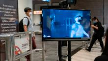 People wearing masks walk past a temperature screening area at Terminal 1 of Changi Airport on March 22, 2020 in Singapore.