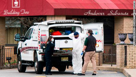 Medical workers put on masks and personal protective equipment while preparing to transport a body at Andover Subacute and Rehabilitation Center on Thursday in Andover, New Jersey.