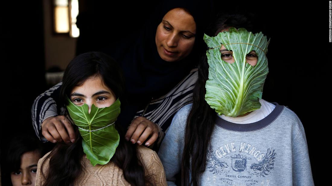 A mother entertains her children with makeshift masks made of cabbage as she cooks in Beit Lahia, Gaza.