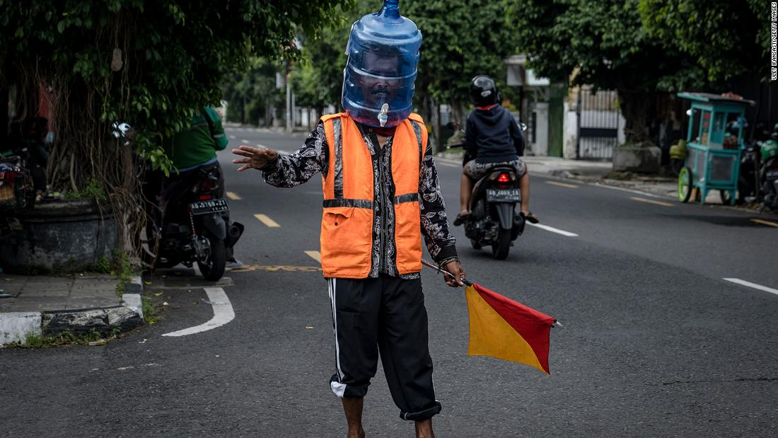 Ali Akbar, a street parking man in Yogyakarta, Indonesia, wears a face shield made from a used water jug.