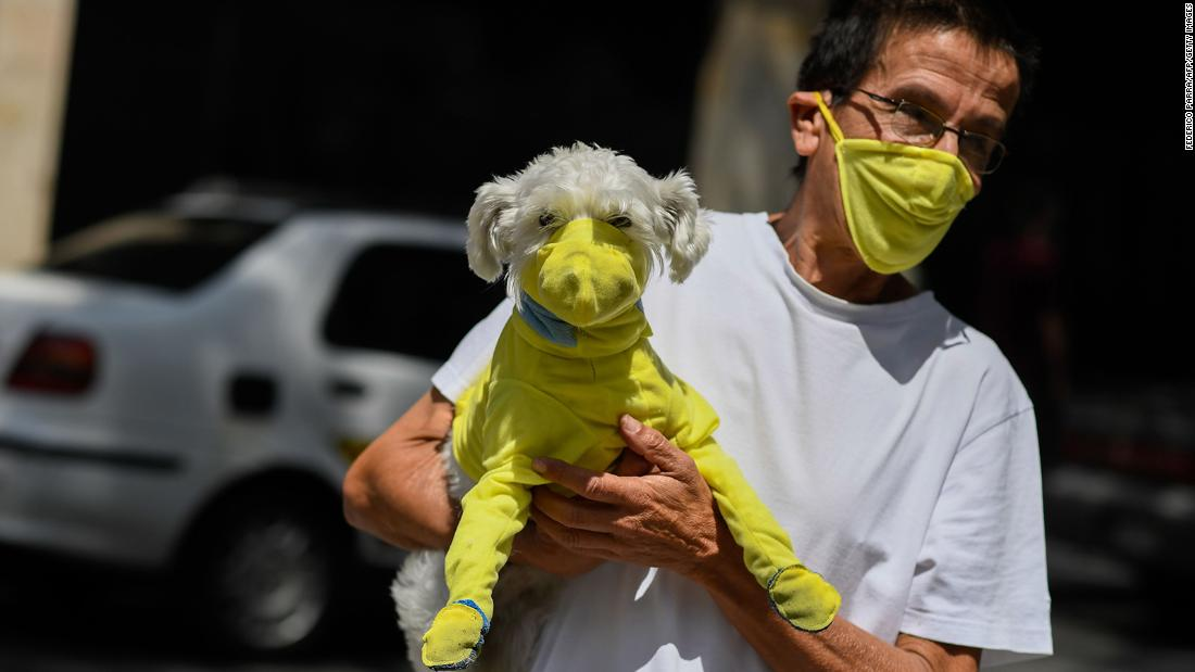 A man in Caracas, Venezuela, wears a face mask while he carries his dog wearing a protective suit.