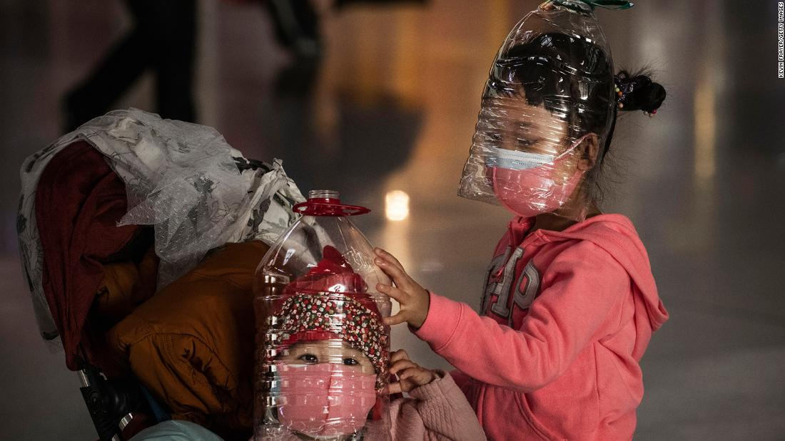 Children wear plastic bottles as makeshift protection while waiting to check in to a flight in Beijing.