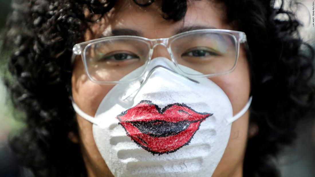 A man in Kuala Lumpur, Malaysia, wears a protective mask featuring a pair of lips.
