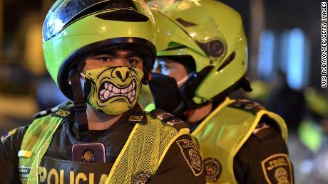 La polizia indossa maschere colorate a Cali, in Colombia, il 20 marzo, con l'avvio di misure preventive.