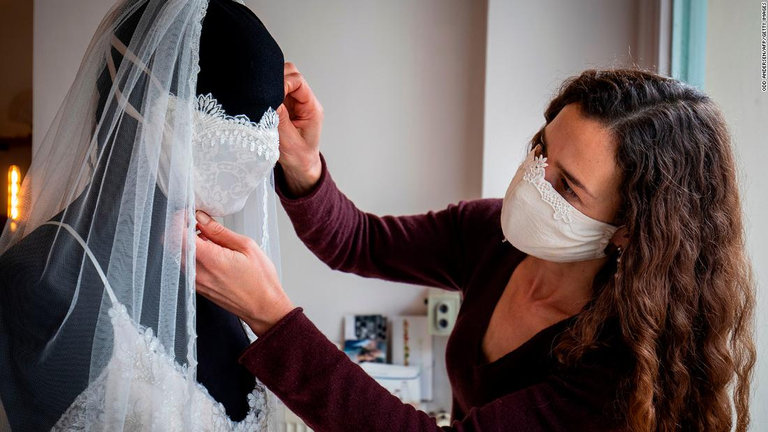 TOPSHOT - Wedding dress and evening wear designer Friederike Jorzig adjusts a mannequin wearing a wedding dress with matching protective mask in her store Chiton in Berlin on March 31, 2020 as the Germany continue to battle the Covid-19 corona virus pandemic. - As all weddings and events have been cancelled, the German fashion designer are creating fashionable facemasks in her workshop, selling them in her shop in Berlin's Schoeneberg district. (Photo by Odd ANDERSEN / AFP) (Photo by ODD ANDERSEN/AFP via Getty Images)