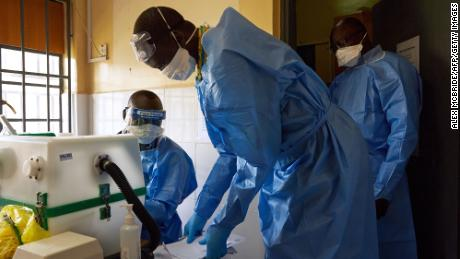 Lab technicians gather around a machine as they test samples for Covid-19 in a laboratory in Juba, South Sudan on April 6.