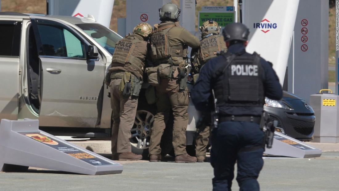 Royal Canadian Mounted Police officers prepare to take a suspect into custody at a gas station in Enfield, Nova Scotia, on Sunday April 19, 2020.
