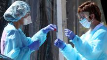 Medical personnel in San Francisco secure a sample from a person at a drive-thru coronavirus testing station in March.  (Photo by Justin Sullivan/Getty Images)