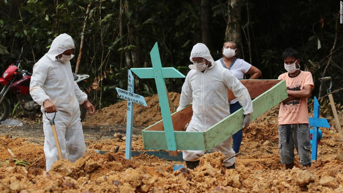 Funeral workers in Manaus, Brazil, prepare the grave of a woman who is suspected to have died from the coronavirus.