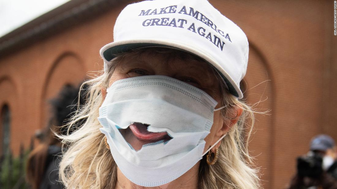 A woman sticks her tongue out of a torn mask at a Reopen Maryland rally outside the State House in Annapolis, Maryland, on April 18, 2020. Residents in multiple states were protesting stay-at-home orders.