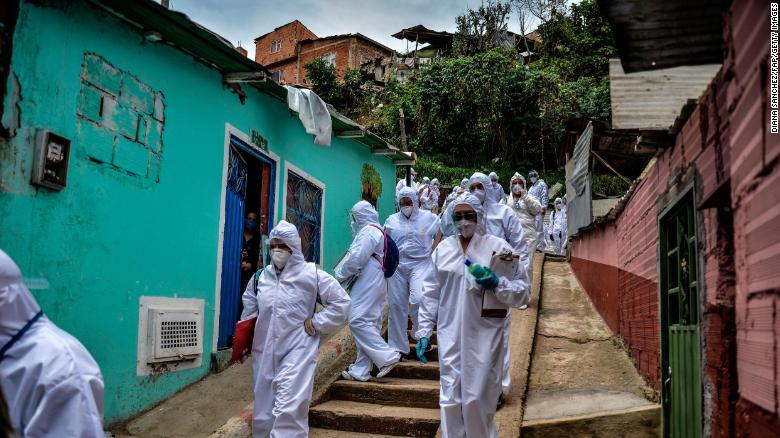 Mayor's office workers wear protective suits as they conduct a census in a Bogota, Colombia neighborhood on April 19, to know how many families need to be provided with food.