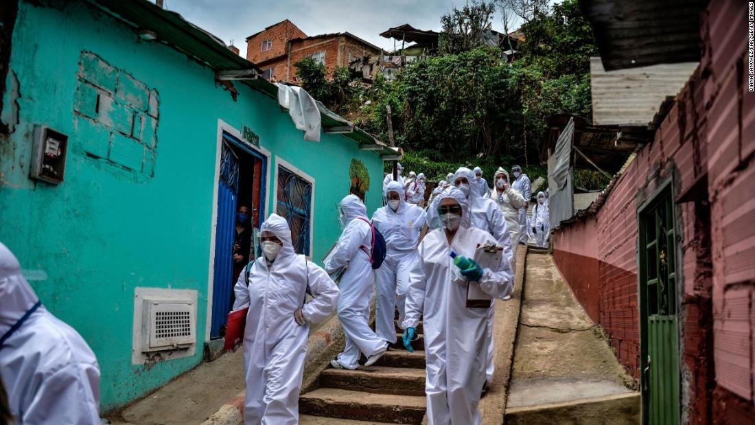 Mayor's office workers wear protective suits as they conduct a census in a Bogota, Colombia, neighborhood on April 19. They were trying to find out how many families needed to be provided with food.
