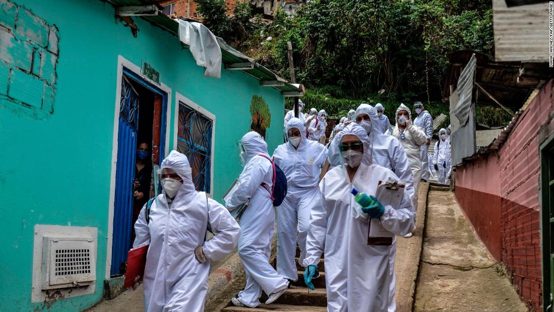 Workers of Bogota's Mayor's office wear protective suits to avoid getting infected with COVID-19 as they conduct a census at Egipto (Egypt) neighbourhood in Bogota on April 19, 2020 to know how many families need to be provided with food to prevent them from go shopping during the new coronavirus pandemic. - The number of coronavirus infections across Latin America surpassed 100,000 on Sunday with nearly 5,000 deaths, according to an AFP tally based on official figures reported by individual countries.