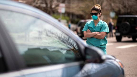 A health care worker  counterprotests at a rally demanding Colorado ease its stay-at-home order.