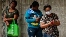 Le donne fanno la fila per entrare in un negozio di alimentari, un giorno in cui gli uomini devono rimanere a Panama City dopo che le autorità hanno assegnato uomini e donne a lavorare tre giorni a settimana separati in cui possono uscire di casa per affari essenziali.