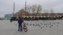 Un uomo con la sua bici circondata da piccioni in una piazza Yenicami quasi vuota al Bazar delle Spezie di Istanbul, in Turchia, durante il blocco del fine settimana.