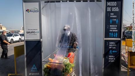 Una persona che indossa una maschera protettiva spinge un carrello della spesa attraverso una camera di decontaminazione nel mercato centrale di frutta e verdura di La Vega a Santiago del Cile.