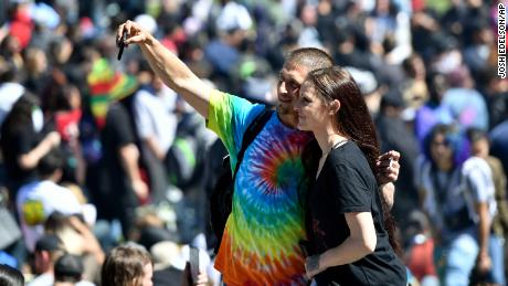 People take a selfie as thousands gather on Hippie Hill in San Francisco, Friday, April 20, 2018. Thousands of people flocked to Hippie Hill for the annual 420 celebration of all things pot and the number that is stoners' code for smoking marijuana. Events also were held in other cities worldwide. (AP Photo/Josh Edelson)