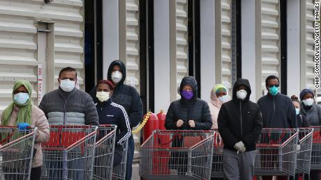 WHEATON, MARYLAND - APRIL 16: Customers wear face masks to prevent the spread of the novel coronavirus as they line up to enter a Costco Wholesale store April 16, 2020 in Wheaton, Maryland. Maryland Governor Larry Hogan ordered that all people must wear some kind of face mask to protect themselves and others from COVID-19 when on public transportation, grocery stores, retail establishments and other places where social distancing is not always possible. (Photo by Chip Somodevilla/Getty Images)
