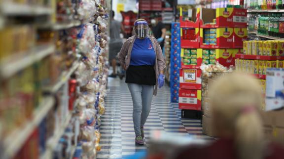 MIAMI, FLORIDA - APRIL 13: Yaleidis Santiago wears a full face shield, mask and gloves as she works at the Presidente Supermarket on April 13, 2020 in Miami, Florida. The employees at Presidente Supermarket, like the rest of America's grocery store workers, are on the front lines of the coronavirus pandemic, helping to keep the nation's residents fed. (Photo by Joe Raedle/Getty Images)
