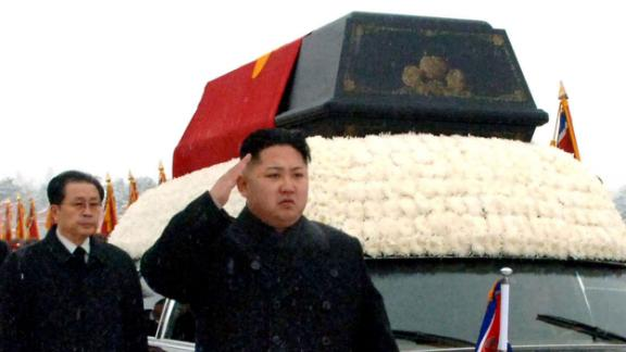 Kim salutes as a hearse carried his father