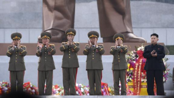 Kim claps as statues of his father and grandfather are unveiled in Pyongyang in April 2012.