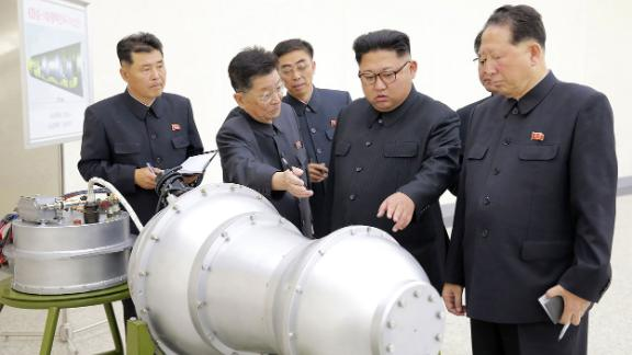Kim looks at a metal casing in this photo provided by North Korea